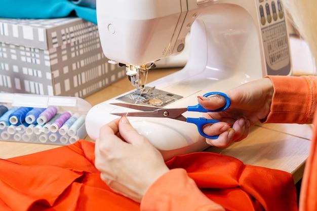 Le mani della sarta tagliano il filo della macchina da cucire, primo piano