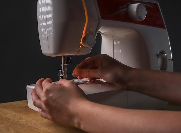 Mani della sarta che inseriscono il filo attraverso il foro dell'ago nella macchina da cucire, iniziando il lavoro.
