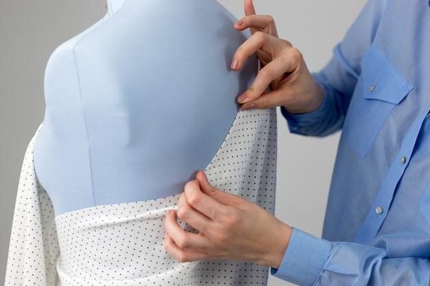 Sarta che misura bellissimo tessuto su manichino sarto blu nel suo laboratorio.