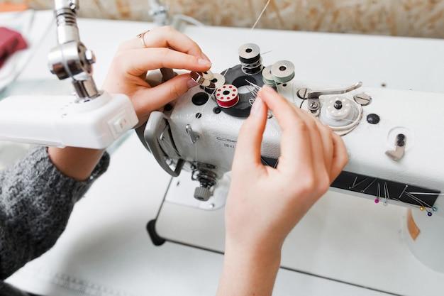 La sarta sostituisce la bobina nella macchina da cucire.