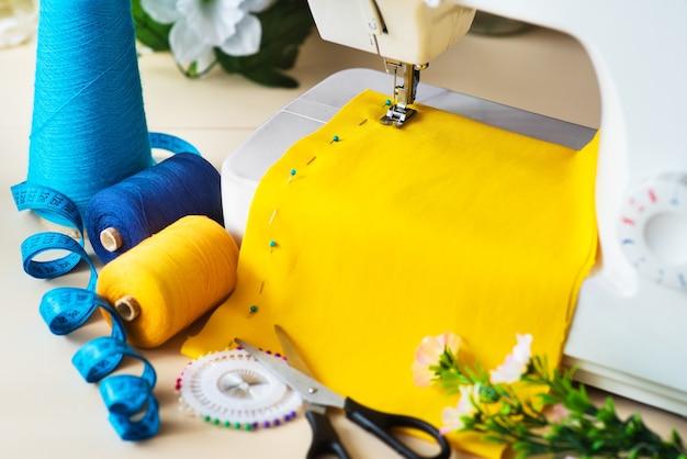 Il posto di lavoro della sarta. macchina da cucire professionale al lavoro. la macchina da cucire cuce tessuti luminosi, metri e fili colorati per cucire