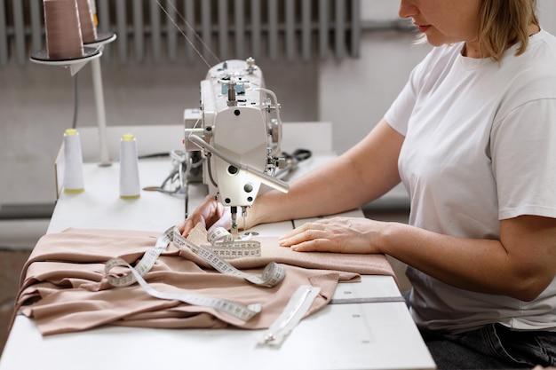 Una sarta dietro una macchina da cucire in una fabbrica