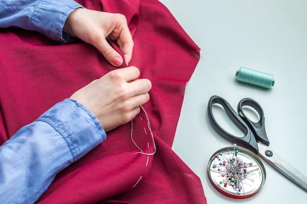 La sarta cuce i vestiti a mano. accessori per cucire. mani di donne