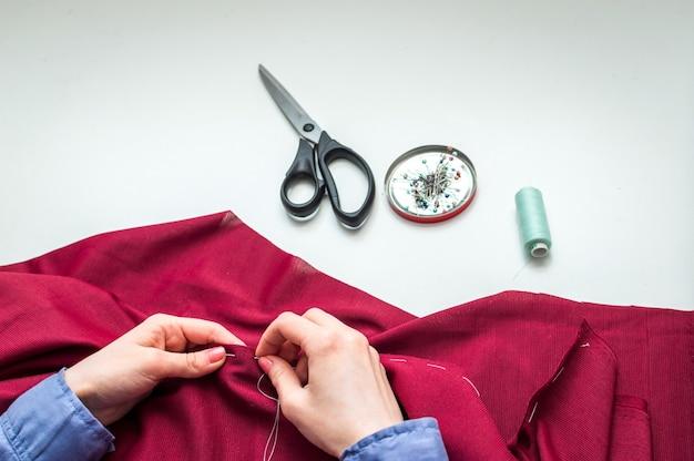 La sarta cuce i vestiti a mano. le mani della donna. avvicinamento. concetto di artigianato.