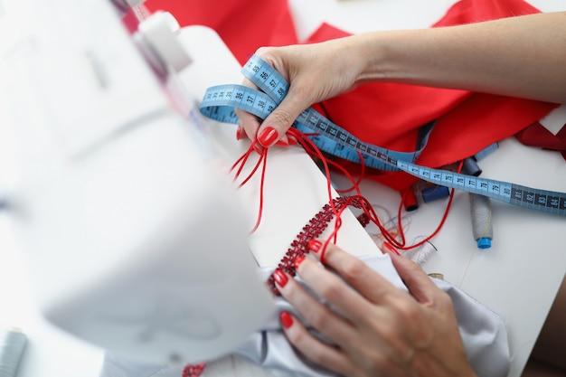 Una sarta si siede a un tavolo da lavoro e tiene i campioni per cucire un prodotto arriva una donna in atelier