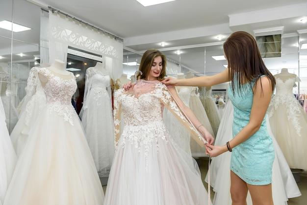 Sarta o consulente di matrimonio aiutando la sposa in salone