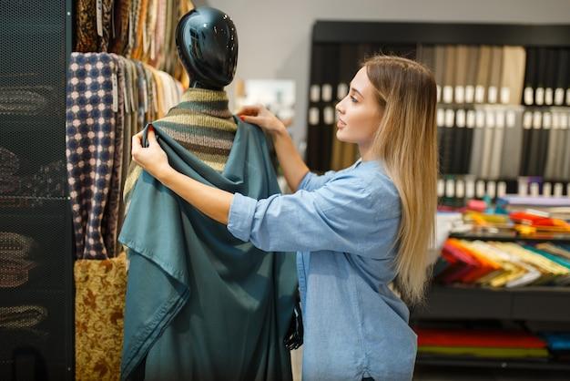 Sarta con tessuto al manichino in negozio di tessuti. donna che sceglie materiale per cucire, sarta in negozio, sarta