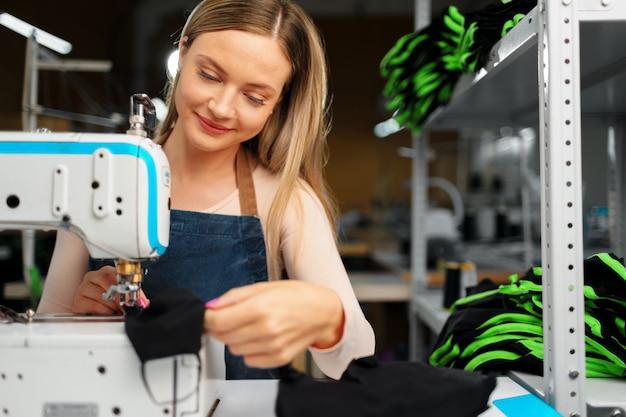 Donna della sarta nel suo luogo di lavoro che cuce i vestiti sulla macchina per cucire