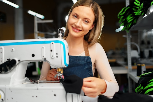 Donna sarta al suo posto di lavoro cucire vestiti sulla macchina da cucire