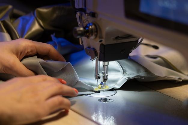 Sarta lavora sulla macchina da cucire closeup donna fashion designer crea nuova collezione di vestiti clothes