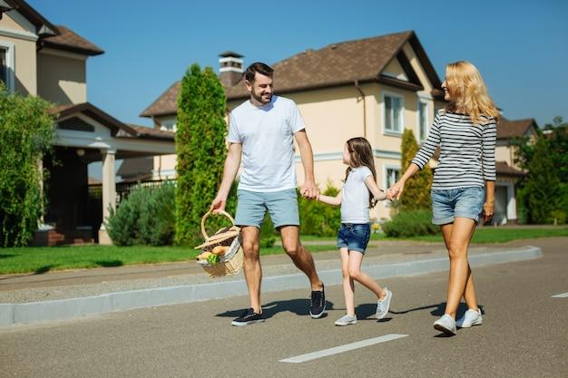 Alla ricerca di avventure. genitori felici e allegri e la loro piccola figlia carina camminano per strada a un picnic mentre l'uomo porta un cesto con il cibo