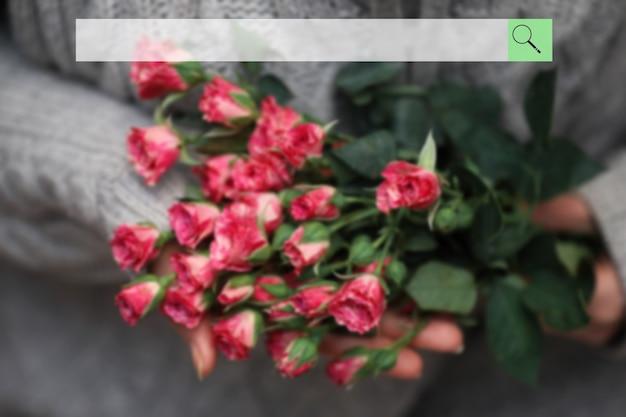Barra di ricerca sullo sfondo del bouquet sfocato di cespugli di rose in mani femminili