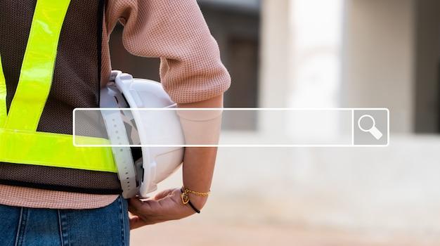 La ricerca della barra di navigazione in internet sullo sfondo è la costruzione di un ingegnere in piedi in un cantiere. ricerca navigazione internet dati informazioni networking concept