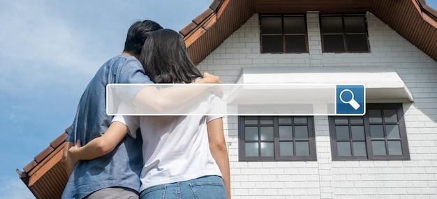 La ricerca della barra di navigazione internet sullo sfondo è coppia felice di fronte alla nuova casa
