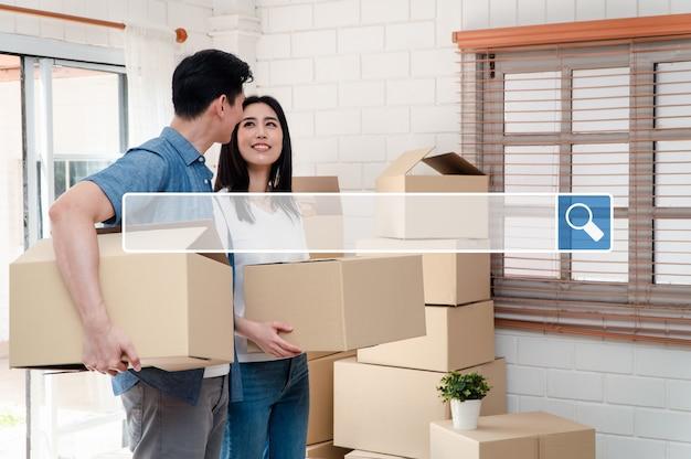 La ricerca della barra di navigazione in internet sullo sfondo è una giovane coppia felice che trasporta scatole di cartone