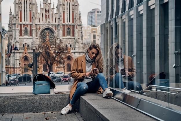 Ricerca della canzone preferita. attraente giovane donna in cappotto che ascolta musica usando il suo smartphone mentre trascorre del tempo spensierato in città
