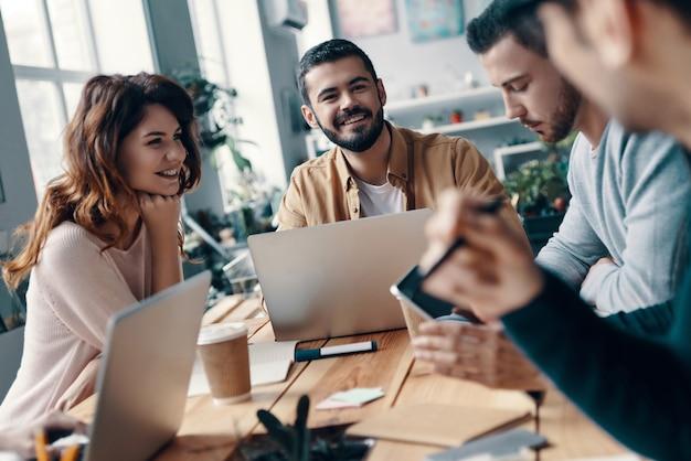 Alla ricerca di nuove idee insieme. gruppo di giovani moderni in abbigliamento casual intelligente che discutono di qualcosa e sorridono mentre lavorano nell'ufficio creativo