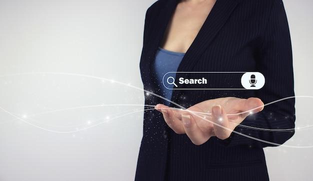 Ricerca di dati di informazioni sul concetto di rete internet. tenere in mano la barra di ricerca dell'ologramma digitale con comando vocale su sfondo grigio. tecnologia di ricerca dei dati.