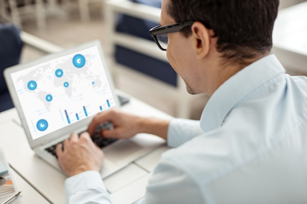 Ricerca in rete. uomo ordinato dai capelli scuri e ben costruito con gli occhiali e che lavora al suo laptop mentre è seduto al tavolo