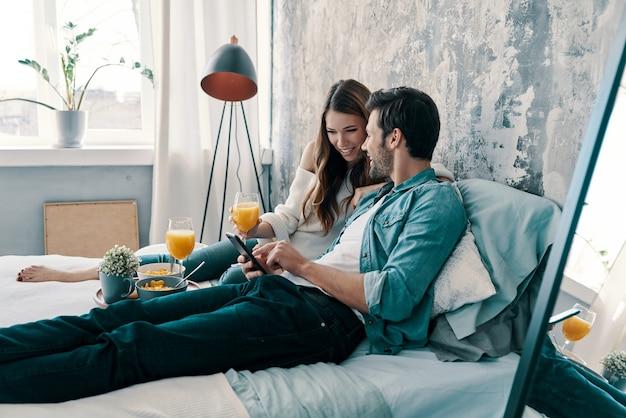 Cercando qualcosa in linea. bella giovane coppia che fa colazione mentre trascorre il tempo a letto a casa