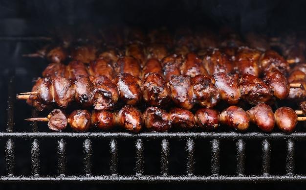 Cuori di yakitori di pollo glassati fumanti brucianti su spiedini di legno su grill all'aperto con griglia metallica metal