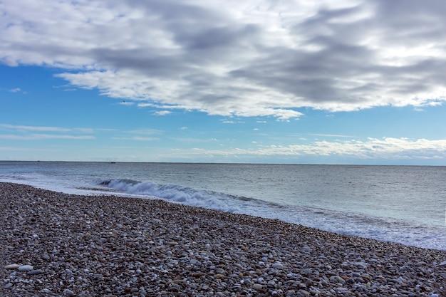 Vista sul mare in maltempo nuvoloso con ciottoli sulla spiaggia su uno sfondo di cielo nuvoloso. mare freddo invernale con piccole onde.