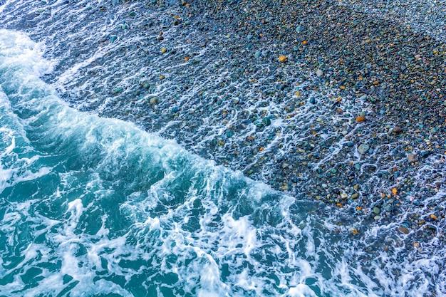 Vista sul mare in maltempo nuvoloso con i ciottoli sulla spiaggia. mare freddo invernale con piccole onde.