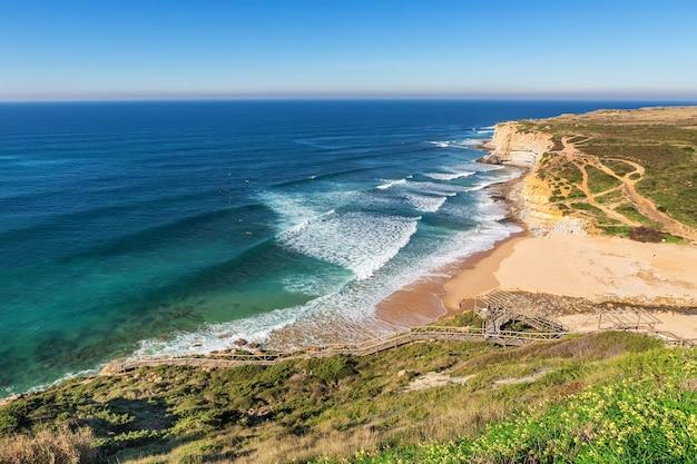 Vista sul mare ericeira portogallo. dai surfisti in acqua.