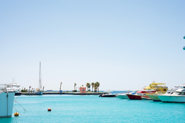 Vista sul mare con parcheggio e barche e navi ancorate.