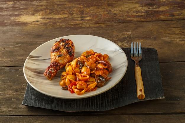 Pasta di conchiglie in un pomodoro con una coscia di pollo al forno su una griglia su un supporto di legno su un tavolo di legno accanto a una forchetta. foto orizzontale