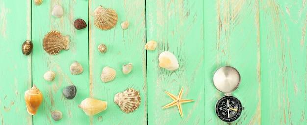 Conchiglie e bussola sulla superficie del tavolo in legno blu