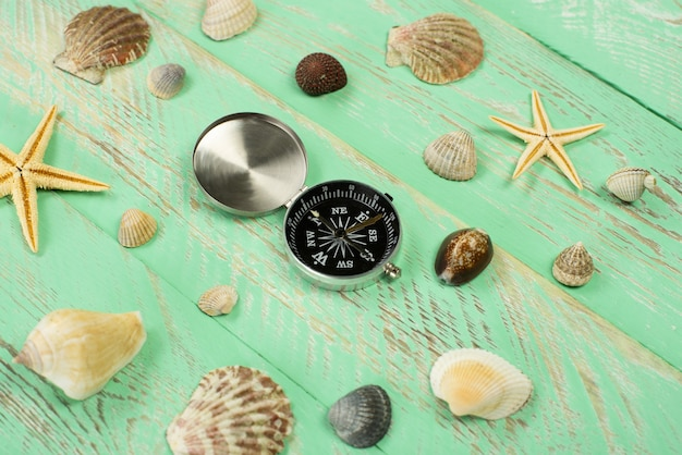 Conchiglie e bussola sulla superficie del tavolo in legno blu Foto Premium