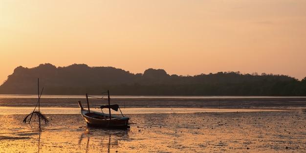 Una spiaggia è circondata da taxi boat thailandesi nel momento del tramonto