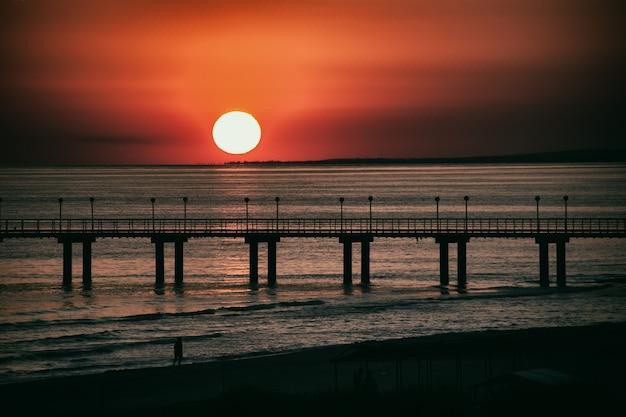 Mare il sole tramonta tramonto i colori del cielo una persona che cammina lungo la spiaggia copia spazio