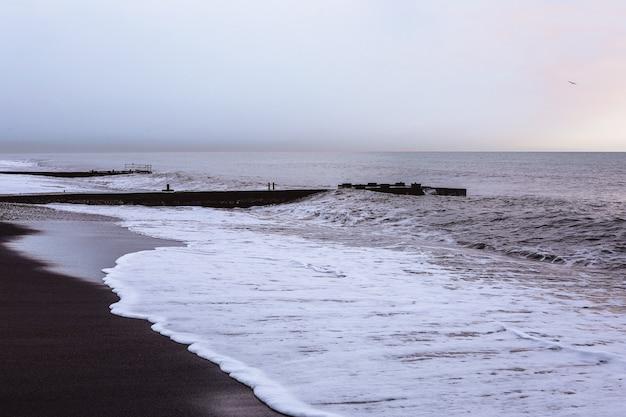 Mare con sabbia nera, schiuma bianca e skyline