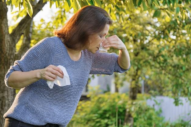 Allergie stagionali, donna con strofinatura nasale, starnuti, asciugandosi il naso all'aperto