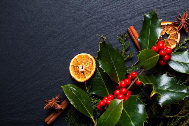 Concetto di sfondo stagionale inverno o spezie natalizie e foglie di agrifoglio di natale e bacche sul bordo di pietra ardesia nera con spazio di copia