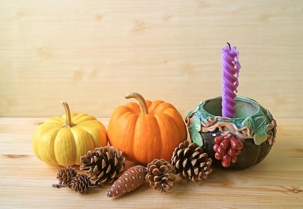 Decorazioni stagionali con zucche, pigne e candela viola
