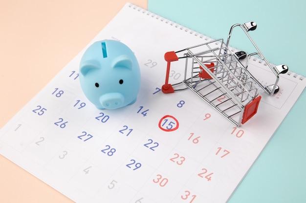 Sconti stagionali. salvadanaio con calendario, carrello del supermercato su un colorato.