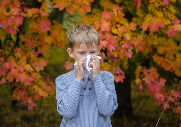 Naso che cola europeo stagionale in un ragazzo europeo. il ragazzo si soffia il naso in un fazzoletto nel parco d'autunno