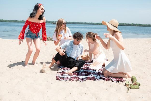 Festa stagionale al gruppo di amici del resort sulla spiaggia che celebrano il riposo divertendosi sulla spiaggia al sole