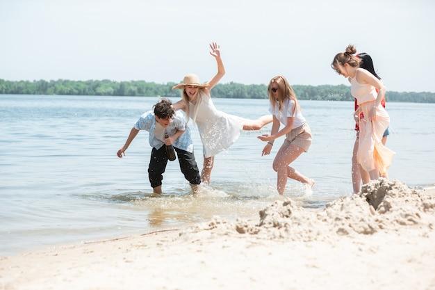 Festa stagionale al resort sulla spiaggia. gruppo di amici che festeggiano, riposano