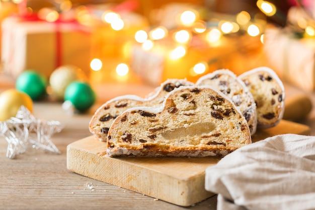 Cibo e bevande stagionali, concetto invernale. torta natalizia tradizionale europea tedesca fatta in casa, dessert di pasticceria stollen su sfondi di legno con decorazioni festive.
