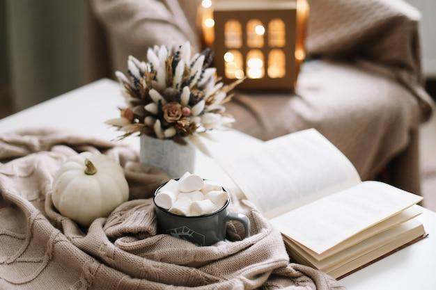 Decorazione autunnale stagionale per la casa con tazza di caffè e fiori secchi e zucca bianca e un libro