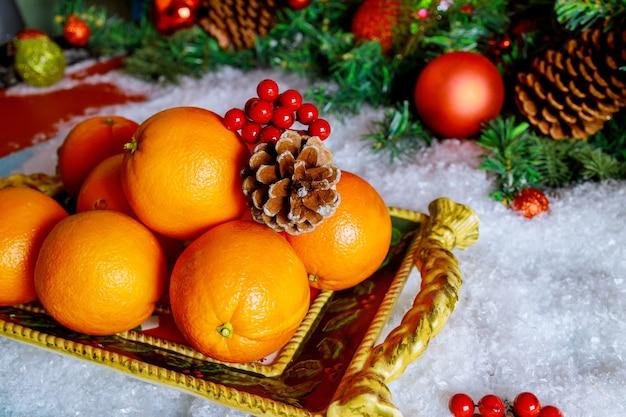 Arance stagionali nel vassoio di natale con ornamento.