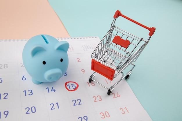Vendita stagionale. salvadanaio con calendario, carrello del supermercato su un colorato.