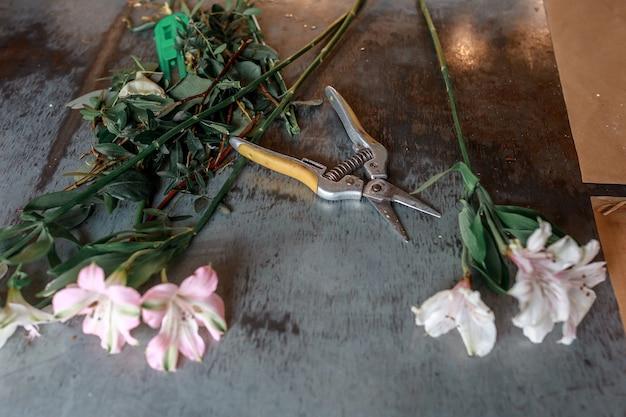 Forbici e fiori sul tavolo di metallo. concetto di disposizione dei fiori, master class.