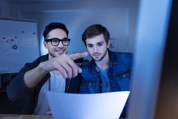 Informazioni segrete. simpatico e felice hacker intelligente che guarda il foglio di carta e inserisce una password durante l'hacking in un sito web del governo