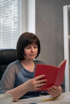 Il segretario scrive i suoi piani nel diario. il capo donna seria nel suo ufficio legge libri o controlla i piani. lavoro d'ufficio.