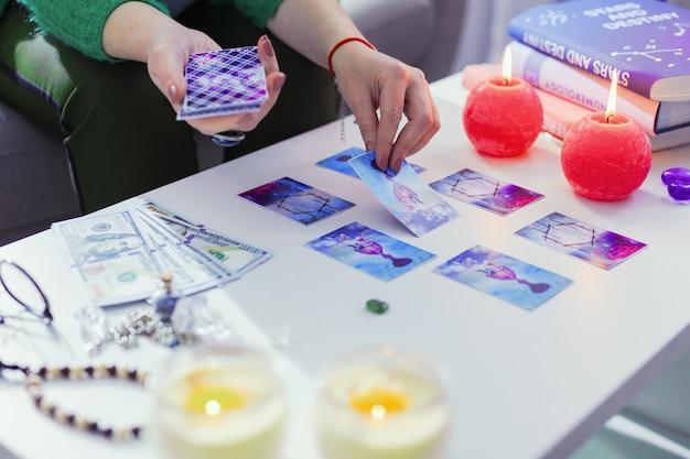 Segreti del futuro. primo piano di carte dei tarocchi magici sul tavolo mentre si guarda al futuro